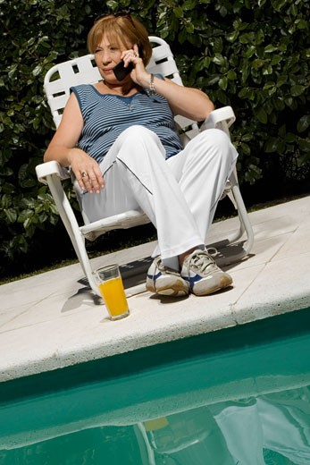 Senior woman talking on a mobile phone at the poolside : Stock Photo