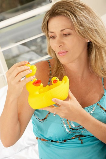 Close-up of a mid adult woman holding rubber ducks : Stock Photo