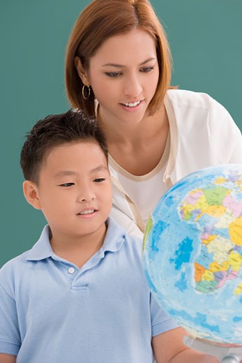 Female teacher with her student looking at a desktop globe : Stock Photo