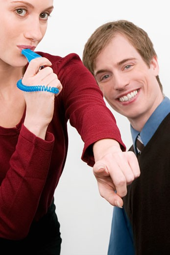 Portrait of a businesswoman blowing a whistle with a businessman standing beside her : Stock Photo