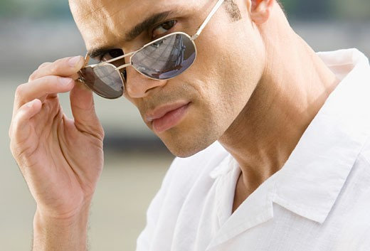 Portrait of a mid adult man adjusting his sunglasses : Stock Photo