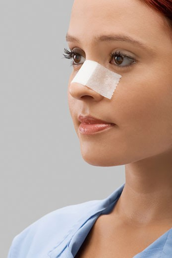 Stock Photo: 1663R-58905 Close-up of a female patient with an adhesive bandage on her nose