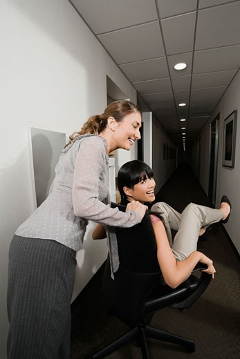 Two businesswomen playing in an office corridor : Stock Photo