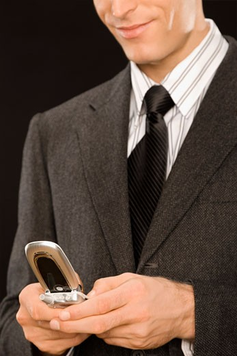 Close-up of a businessman text messaging : Stock Photo
