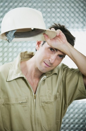 Stock Photo: 1663R-59898 Portrait of a mid adult man holding a hardhat and wiping his forehead