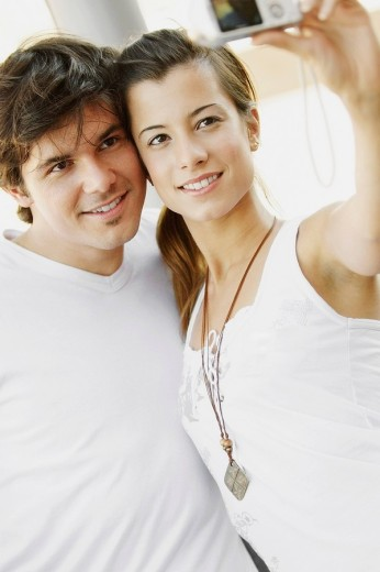 Close_up of a young couple taking a photograph of themselves : Stock Photo