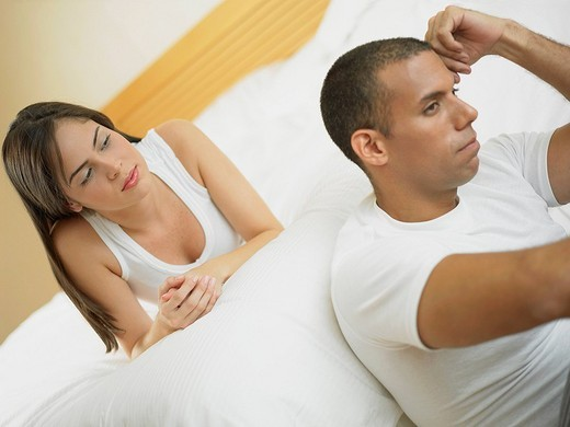Close_up of a mid adult man thinking with a young woman lying on the bed : Stock Photo