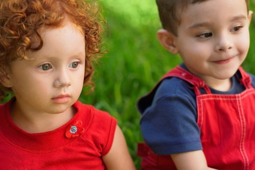 Close_up of a girl and her brother sitting on the grass : Stock Photo