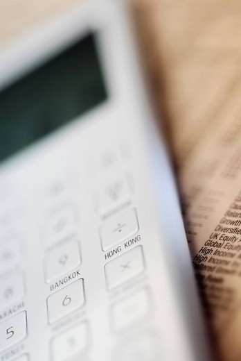 Close_up of a calculator on a financial newspaper : Stock Photo