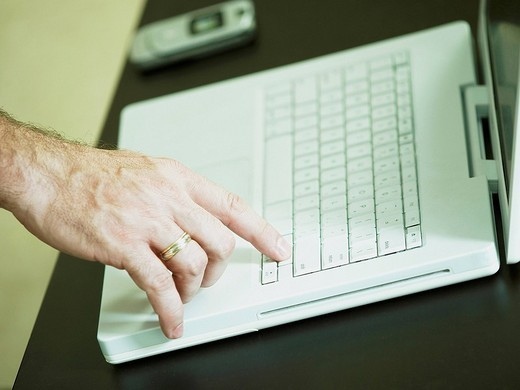 Close_up of a man´s finger on a laptop : Stock Photo