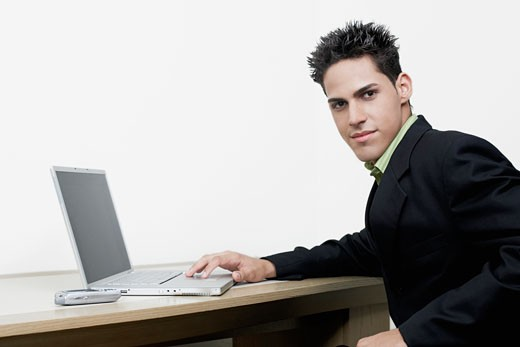 Portrait of a businessman sitting in front of a laptop : Stock Photo