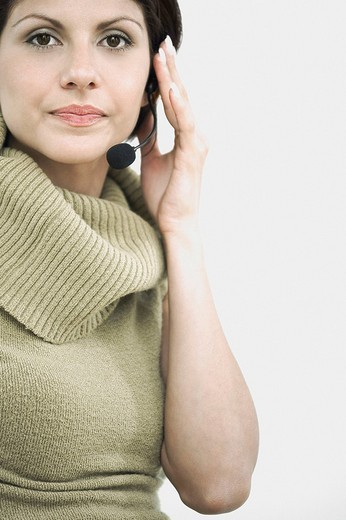 Portrait of a young woman using a headset : Stock Photo