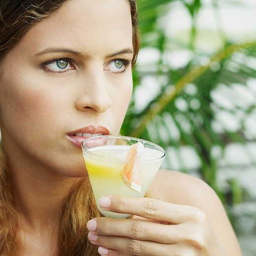 Stock Photo: 1663R-63357 Close_up of a young woman holding a glass of juice