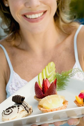 Close-up of a young woman holding assorted tarts with an eclair in a platter : Stock Photo