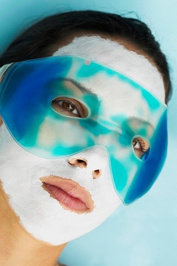 Close_up of a young woman with a facial mask and an eye mask on her face : Stock Photo