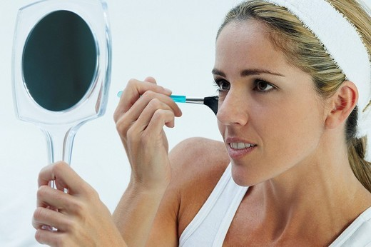 Stock Photo: 1663R-64199 Close_up of a mid adult woman applying make_up on her face