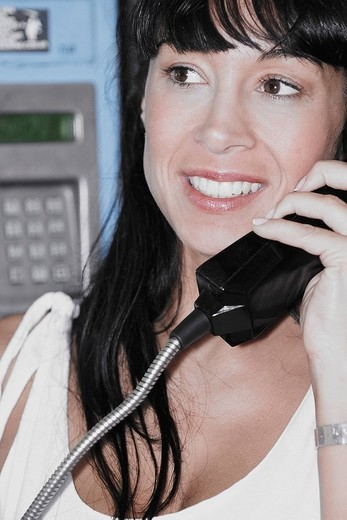 Close_up of a mid adult woman holding a telephone receiver : Stock Photo