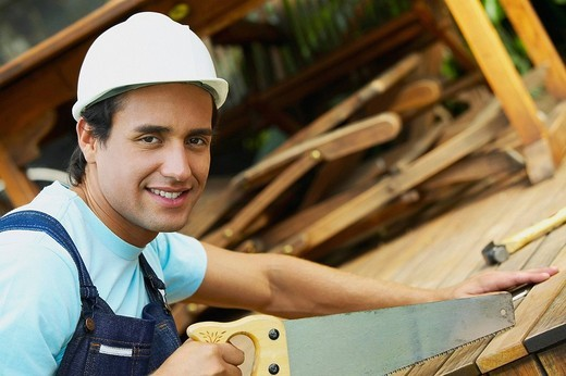 Stock Photo: 1663R-64541 Portrait of a carpenter cutting a plank with a saw