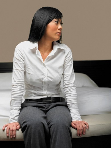 Stock Photo: 1663R-64543 Mid adult woman sitting on the bed and thinking