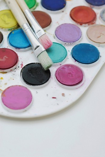 Close_up of a color palette with paintbrushes : Stock Photo