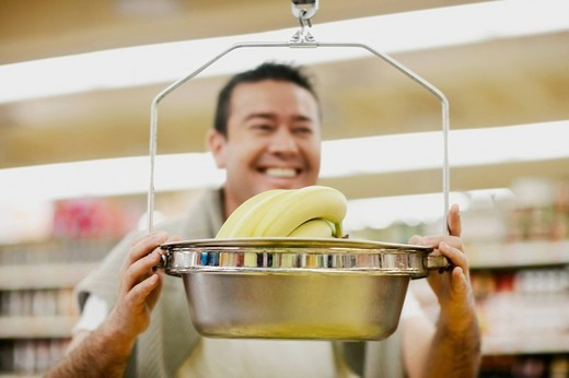 Close_up of a mid adult man holding a weighing scale and smiling : Stock Photo
