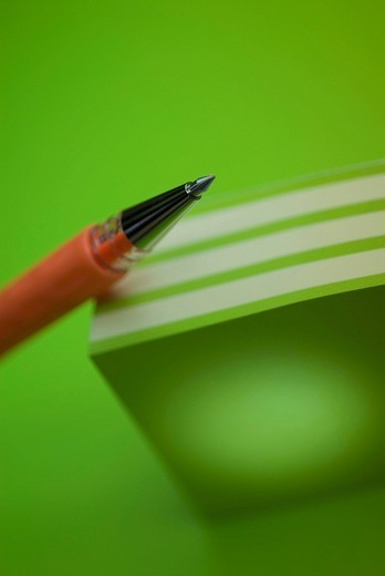 Close_up of a pen on a stack of colored post_it notes : Stock Photo