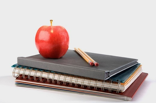 Close_up of an apple with two pencils on notebooks : Stock Photo
