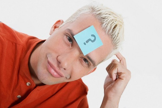 Portrait of a young man smirking with an adhesive note on his forehead : Stock Photo