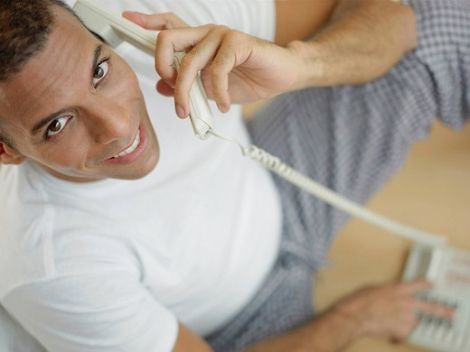 Portrait of a mid adult man talking on the telephone and smiling : Stock Photo