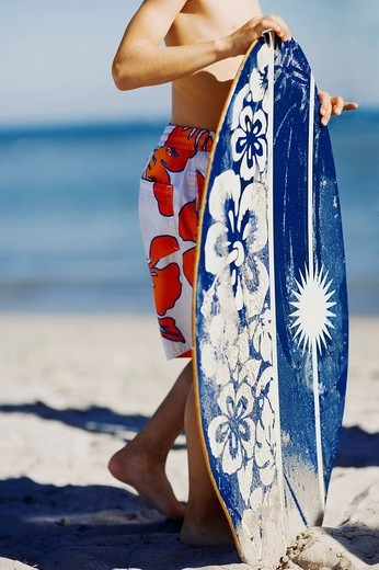 Low section view of a boy holding a boogie board on the beach : Stock Photo
