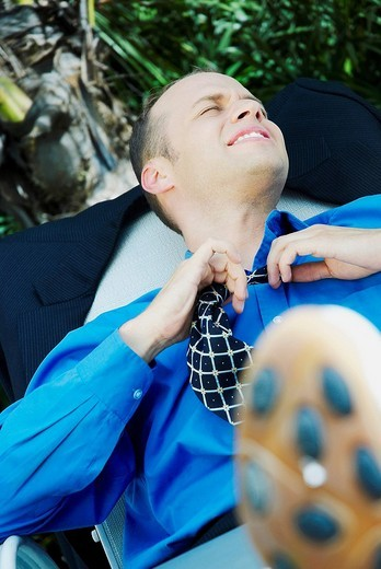 Businessman reclining on a lounge chair and loosening his tie : Stock Photo