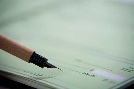 Close_up of a fountain pen on a check : Stock Photo