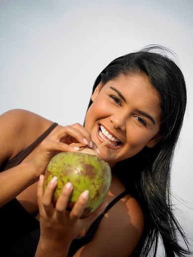 Portrait of a young woman sipping juice from coconut : Stock Photo