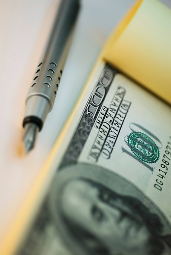 Stock Photo: 1663R-66982 Close_up of a fountain pen and one hundred dollar bill