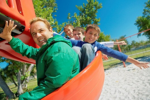 Mid adult man on a slide with three children : Stock Photo