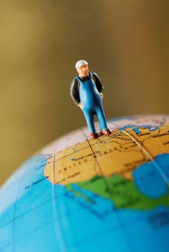 Close_up of a figurine on a globe : Stock Photo