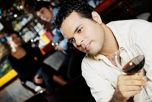 Close_up of a young man holding a glass of wine : Stock Photo