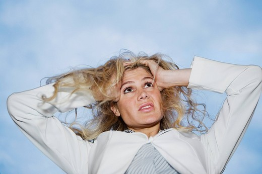Low angle view of a businesswoman pulling her hair in frustration : Stock Photo