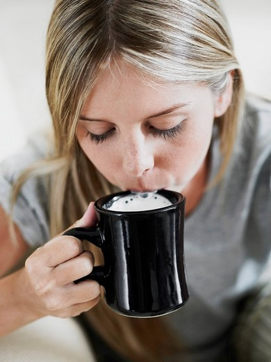 Close_up of a young woman drinking coffee : Stock Photo