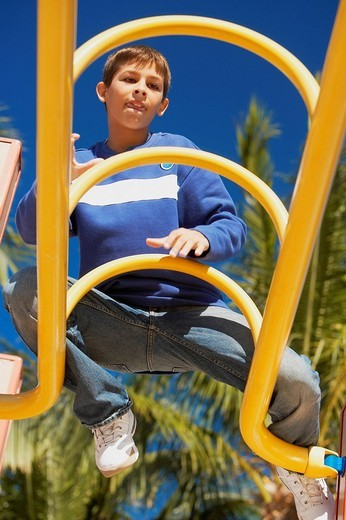 Low angle view of a teenage boy sitting on a jungle gym : Stock Photo