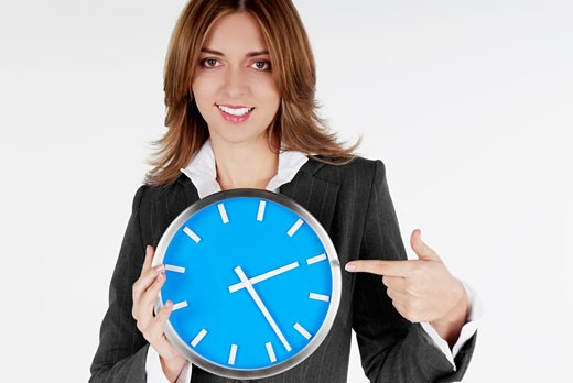 Stock Photo: 1663R-6757 Portrait of a businesswoman pointing at a clock and smiling