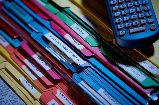 Close_up of a remote control on a stack of files : Stock Photo