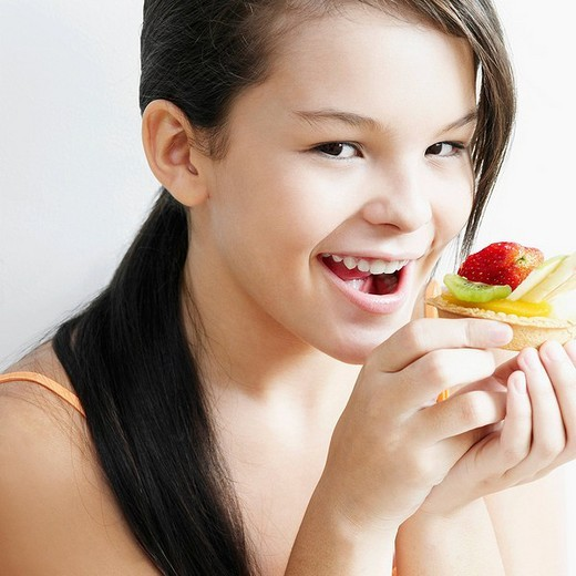 Portrait of a teenage girl holding a fruit tart and smiling : Stock Photo