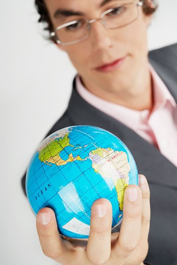 Close-up of a businessman holding a globe : Stock Photo