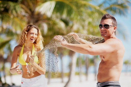 Young couple standing on the beach and holding a fishing net : Stock Photo