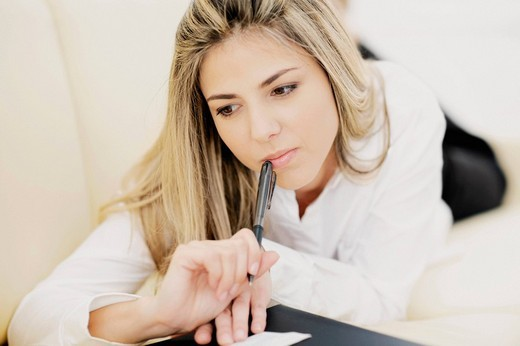 Close_up of a mid adult woman holding a pen and thinking : Stock Photo