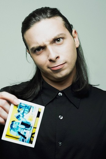 Stock Photo: 1663R-68802 Portrait of a young man holding a playing card