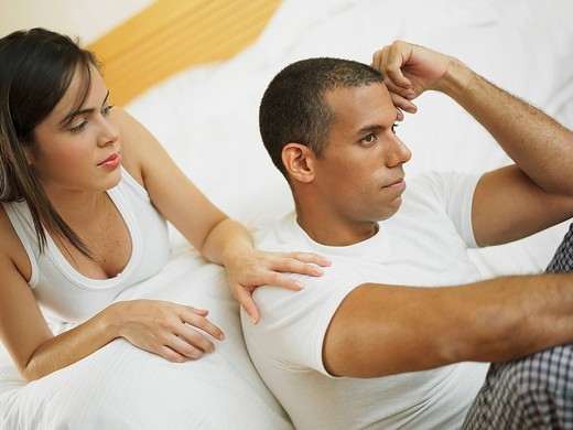Stock Photo: 1663R-68840 Close_up of a mid adult man thinking with a young woman lying on the bed