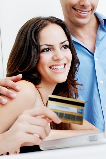Close-up of a young couple doing online shopping : Stock Photo