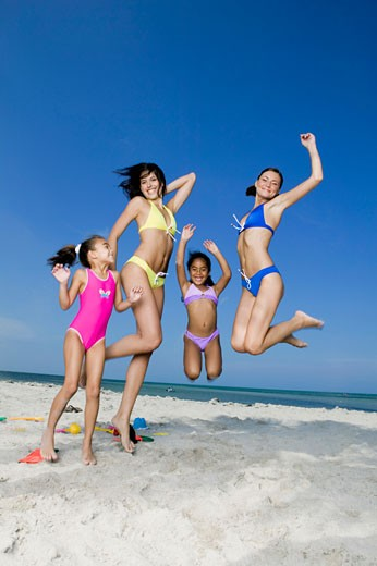 Stock Photo: 1663R-7133 Two young women and two girls jumping on the beach